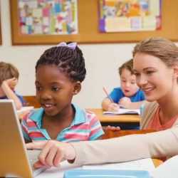 Female Teacher Showing Girl Laptop Screen Sitting At Table Smiling