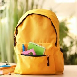 Yellow Backpack With School Supplies Visible From Pocket