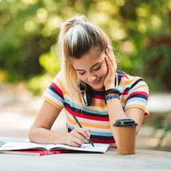 Teenage Girl With Striped Shirt Smiling While Writing In A Notebook