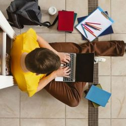 Overhead View Of Male Student Sitting On Floor Using Laptop With Backpack C Coffee C Textbooks C And Pencils Around Him