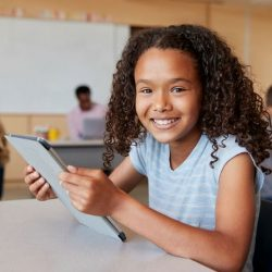 Female Student Of Color Holding Tablet And Smiling