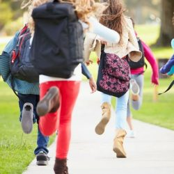 Group Of Students Excitedly Running On Sidewalk
