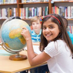 Smiling Student Pointing At A Globe In A Library