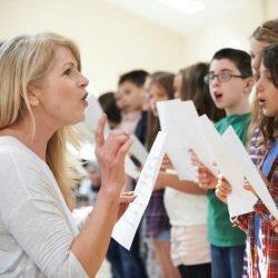 Choir Teacher Coaching Students To Sing