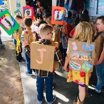 Kindergarten students with handmade alphabet vests