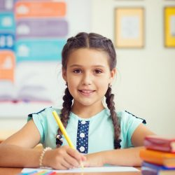 Smiling Girl Writing With Textbooks Beside Her