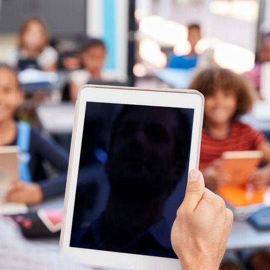 Teacher Holding Tablet In Front Of Class