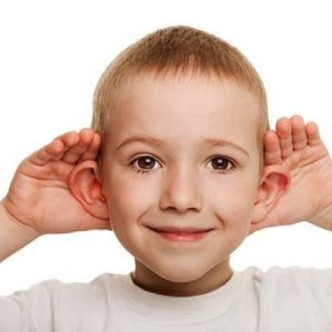 Young boy with hands behind his ears